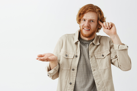 Studio shot of pissed confused and displeased caucasian redhead guy with beard rolling index finger on temple and shrugging with disappointed and shocked expression looking at stupid employee Stock Photo
