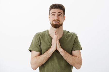 Indoor shot of cute boyfriend praying god looking up as holding palms together in pray over chest making wish, supplicating, hopefully anticipating dream come true over white background, begging Stock Photo