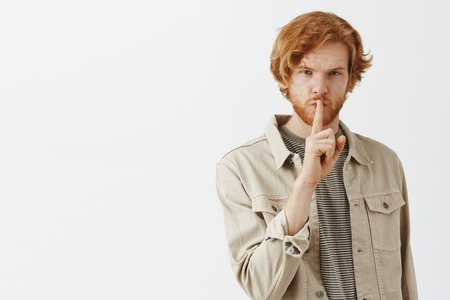 Portrait of mysterious good-looking young redhead  caucasian guy in beige jacket over t-shirt showing shush gesture with index finger over mouth looking serious