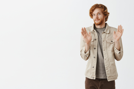 Portrait of intense redhead male with beard feeling awkward smiling tight from discomfort raising palms in surrender and turning away from camera refusing or apologizing Stock Photo