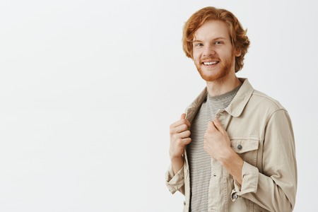 Man turning near mirror liking new outfit getting dressed for tonight date. Portrait of pleased happy redhead male model with beard trying on new clothes touching jacket and smiling broadly satisfied Stock Photo
