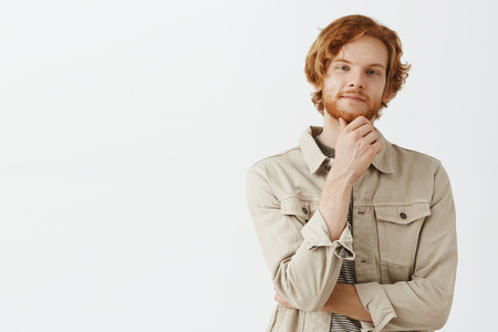 Intrigued and satisfied good-looking male entrepreneur with red wavy hair rubbing beard on chin and smiling with pleased look at camera thinking having good idea or liking what he observes