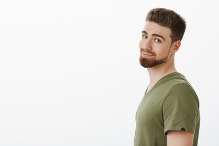 CLose-up shot of charming charismatic bearded boyfriend in t-shirt standing in profile turning head at camera and grinning delighted and carefree posing happy against white background