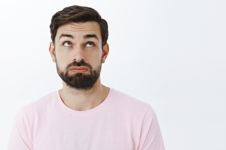Close-up shot of unlucky, tired and upset attractive young bearded male with beard raising eyebrows in despair looking up with regret and disappointment, standing unconfident and exhausted