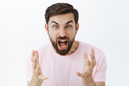 Pissed guy yelling from anger and hate during argument. Portrait of outraged pressured caucasian male with beard screaming and gesturing with itense hands with hate and disgust over white background