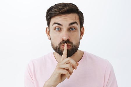 Gentle, tender attractive father with beard in pink t-shirt folding lips as shushing at camera holding index finger over mouth raising eyebrows, asking keep quiet or keep secret