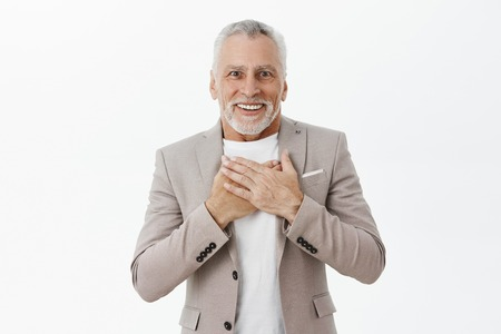 Old man receiving heartwarming and touching gift pleased and delighted smiling with crooked teeth at camera holding hands on chest in grateful and surprised gesture being happy to bottom of heart Stock Photo