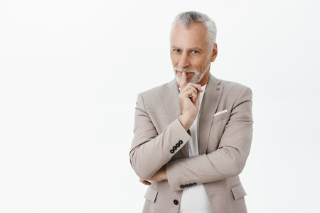 Enthusiastic and creative charming senior businessman with white hair and moustache in elegant stylish grey suit showing shh gesture with index finger over mouth smiling tricky having plan or surprise