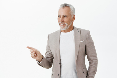 Realxed and amused good-looking senior male entrepreneur in grey suit over t-shirt looking and pointing left with happy satisfied smile liking new product of company presented on copy space