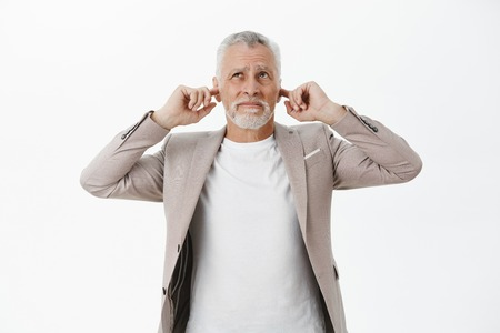 Portrait of old businessman being disturbed by loud noise comming upwards closing ears with index fingers like earplugs looking up worried and displeased wish sound or yell over white background