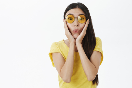 Impressed speechless woman overreacting to surprise folding lips in wow sound touching cheeks from amazement wearing stylish sunglasses, yellow t-shirt being astonished and delighted with awesome news