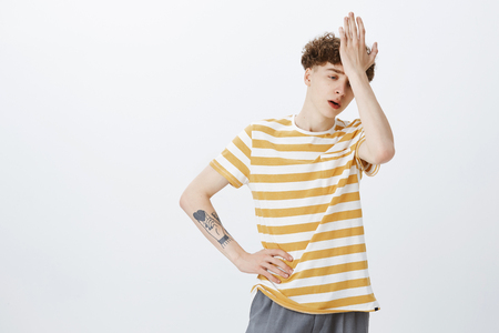 Oh gosh why me. Portrait of uneasy bothered and fed up young teenage boy with curly hairstyle and tattoo on arm punching forehead with palm looking drained and tired as standing over gray wall