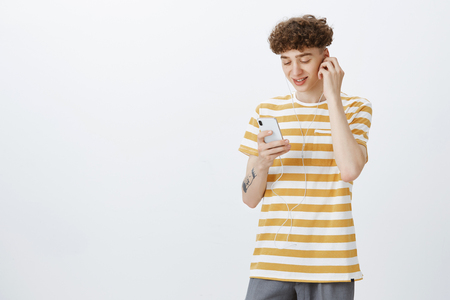 Delighted and carefree modern young man with trendy curly haircut and tattoos smiling broadly as watching awesome video in online app via smartphone wearing earphones not disturb anyone with noise Imagens - 114680181