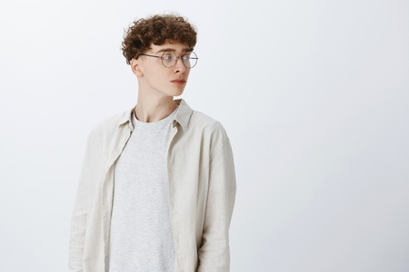 Handsome young hipster guy in round glasses with brown curly hair turning right with intrigued and curious expression looking calm being confident and self-aware over gray background