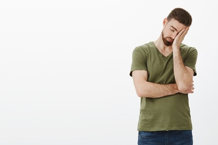 Oh gosh how tiresome. Portrait of tired and drained male workaholic with beard leaning on palm as making facepalm sign, close eyes exhausted and drained posing upset and uneasy over white background