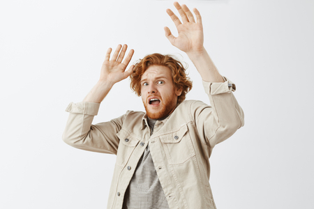 Studio shot of frightened timid redhead guy was scared by friend raising palms in surrender falling backwards with terrifyis shocked expression standing in panic over gray background