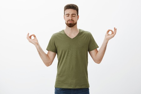 Calming down and releasing stress with meditation. Determined and relaxed attractive bearded guy in olive t-shirt holding hands in lotus pose reaching nirvana, close eyes and smile delighted