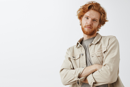 Oh not impressive. Portrait of cool snobbish redhead guy with wavy hair and beard tilting backwards with hands crossed on chest and doubtful unimpressed expression being disappointed Stok Fotoğraf
