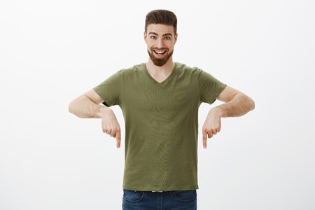 Hey hurry and check out promo. Portrait of excited overhwhelmed happy young bearded guy smiling amazed and pointing down with index fingers as if giving hint or indicating awesome copy space