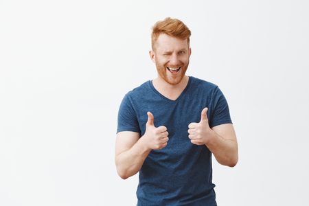 Yeah boy nice choice. Portrait of good-looking male friend with ginger hair showing thumbs up and winking with hint, liking and supporting great decision, cheering over gray background Stock Photo