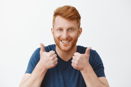 Supportive and attractive adult redhead male with bristle liking great plan raising hands, showing thumbs up, smiling joyfully, accepting nice idea or cheering friend who trying talk to charming woman