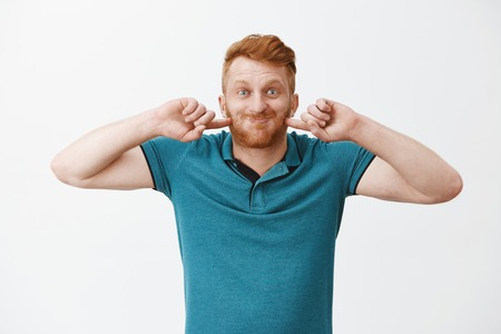 Funny and happy redhead mature dad playing with son, puffing up, holding breath and poking cheeks while smiling broadly, fooling around and making faces over gray background