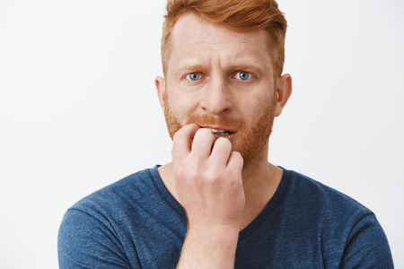 Redhead husband worried, feeling scared wife found out his hiding place where he keeps salary, biting fingernails and staring nervously at camera, waiting for result and feeling anxious about it
