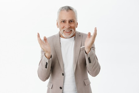 Portrait of excited enthusiastic old male gambler in suit making bet clapping hands with amazement and joy smiling broadly looking thrilled and astonished at camera posing amused over gray background Stock Photo