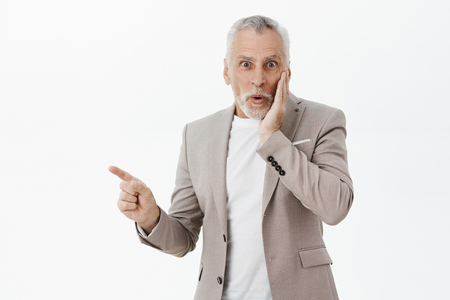 Waist-up shot of amused enthusiastic and happy good-looking fancy old man with beard and grey hair pressing hand to cheek from surprise and amazement pointing left and smiling feeling astonished Reklamní fotografie