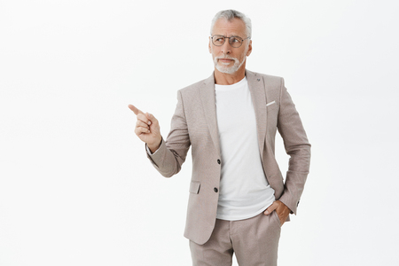 Unretouched shot of good-looking intelligent and elegant old man with grey beard and hair holding hand in pocket pointing and looking at upper left corner with questioned uncertain and disliking look
