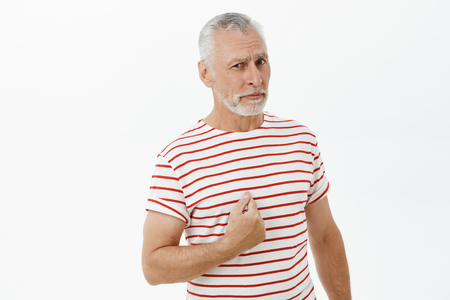 You talking to me. Portrait of confused and unsure good-looking senior bearded male with grey hair and moustache in striped t-shirt pointing at himself with raised eyebrow being picked over grey wall