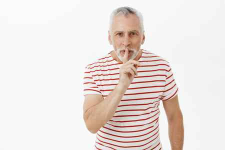Shh I preper surprise for wife. Portrait of charming charismatic happy male pensioner in striped t-shirt with grey beard and hair bending towards camera in shush gesture asking keep secret