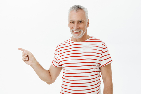 Waist-up shot of delighted carefree charismatic happy old man with grey beard in striped t-shirt smiling satisfied and confident pointing left showing perfect copy space over gray background