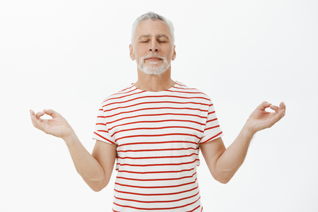 Old man taking deep breath peacefully meditating over gray background. Portrait of determined and calm good-looking senior male with grey beard standing in lotus pose with closed eyes practicing yoga