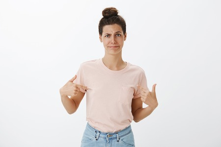 Insecure and unconfient woman complaining friend she is not good candidate being displeased with own outfit pointing at herself with index fingers, frowning and smirking unsure and doubtful Stock Photo