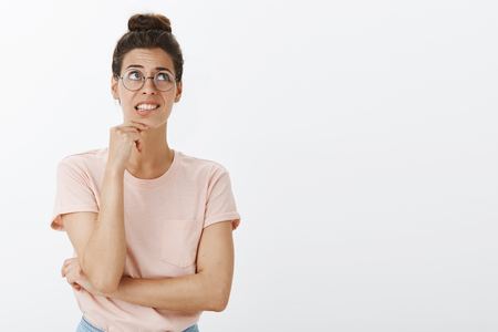 Nervous insecure and unconfident young smart european female in glasses and hair bun clenching teeth awkward and worried looking at upper right corner as feeling anxious not knowing answer