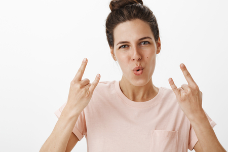 Girls rock this world. Portrait of energized and confident good-looking woman showing rock-n-roll gesture folding lips in cheer making self-assured expression as having fun at party over gray wall