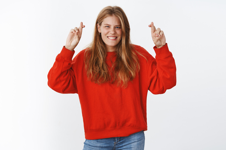 Charismatic and optimistic young european woman in red oversized sweater raising hands with crossed fingers for good luck smiling broadly feeling fortune and luck on her side, faith in win and success