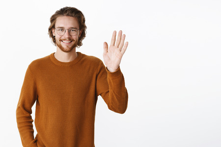 Waist-up shot of charming friendly man saying hi as waving with raised palm and smiling meeting new people smiling broadly welcoming members standing pleased and relaxed over gray background