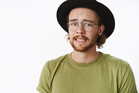 Yikes, I am in trouble. Portrait of worried sad cute guy with beard in glasses and hat frowning clenching teeth, feeling guilty as making bad thing to friend standing nervous over gray background Stock Photo