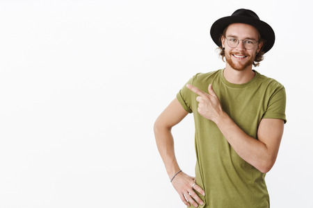 Waist-up shot of energized happy and confident young handsome bearded male in glasses, black hat and t-shirt holding hand on waist pointing at upper left corner proudly, leading way