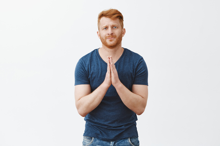 Please I really need your help. Portrait of attractive and cute redhead bearded male in casual outfit, holding hands in pray and pursing lips while begging for favor or apology over gray background