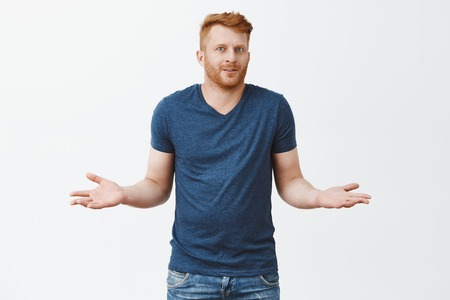 Man pretends he know anything, shrugging, making clueless expression. Portrait of unaware handsome masculine redhead male with bristle, holding hands aside, smiling, feeling confused and uncertain