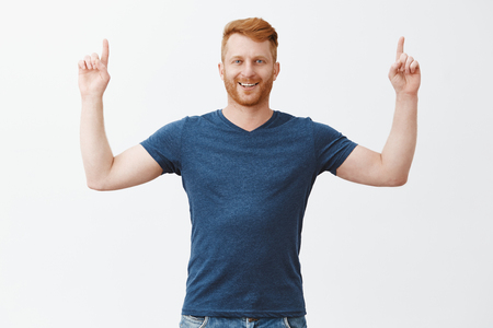 Proudly showing great concept upwards. Portrait of good-looking confident and happy european guy with bristle, raising hands and pointing up with pleased and satisfied expression, feeling great Stock Photo