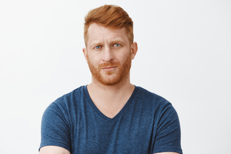 You talking bullshit, doubt can trust you. Unsure displeased redhead mature male entrepreneur looking suspiciously at camera with raised eyebrows and serious face, unimpressed or showing disbelief