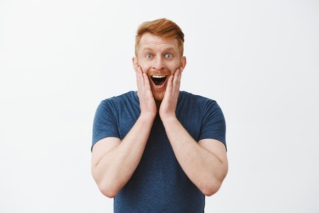 Husband found out wife pregnant, being happy and excited. Joyful attractive redhead male with bristle, holding palms on cheeks and smiling joyfully, being charmed with amazing and pleasant scene