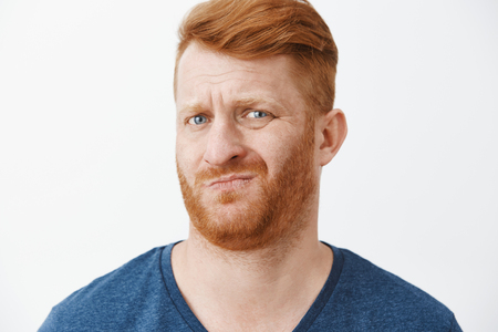 Sounds suspicious and gross. Portrait of unsure displeased funny redhead with cool hairstyle, frowning, smirking and wrinkling nose from dislike, looking doubtful at new meal wife made
