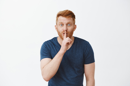 Hey, wanna hear my secret. Handsome enthusiastic redhead unshaven masculine male model being thrilled with great news, saying shh while showing shush gesture, wanting make surprise over grey wall