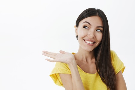 Girl showing product changed her life. Portrait of joyful pleased cute european female with dark hair in trendy yellow t-shirt stooping pointing left with arm near shoulder and smiling satisfied