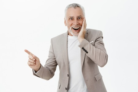 Waist-up shot of speechless delighted and surprised handsome elegant grandfather in stylish suit pressing hand to cheek from amazement and joy pointing left at curious thing smiling happily